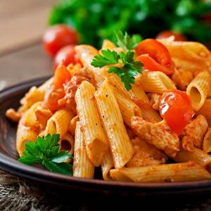 Penne pasta in tomato sauce with chicken, tomatoes decorated wit